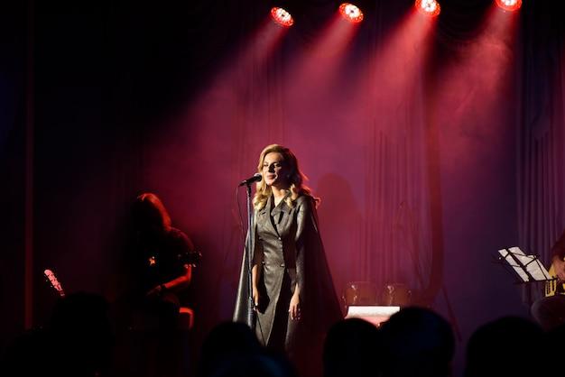 Piosenkarka z mikrofonem na scenie w oświetleniu scenicznym.