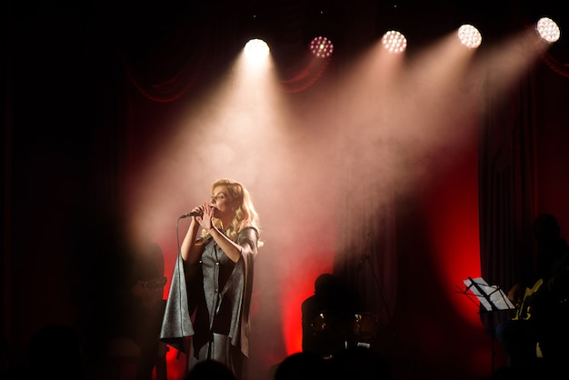 Piosenkarka ze swoim zespołem występującym na scenie. koncert. widok z audytorium.