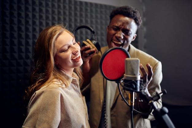 Piosenkarki płci męskiej i żeńskiej w słuchawkach śpiewają piosenkę o mikrofon, wnętrze studia nagrań na tle. profesjonalny zapis głosu, miejsce pracy muzyka, proces twórczy, nowoczesna technologia audio audio