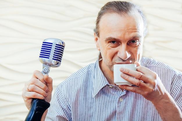Piosenkarz mężczyzna z staromodnym mikrofonem pije filiżankę kawy