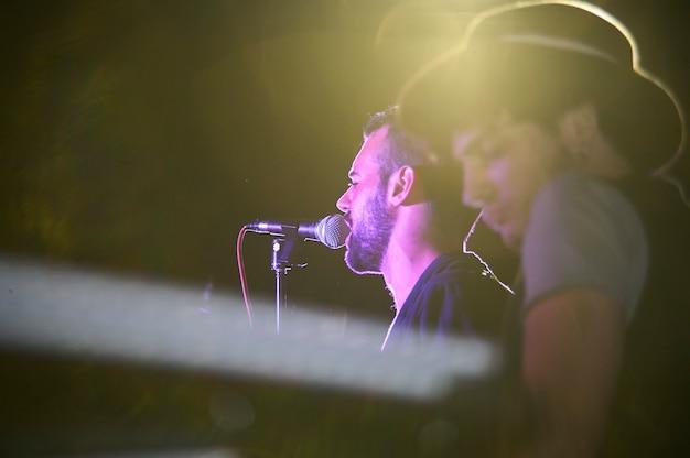 Piosenkarz pod kolorowymi światłami i spotami