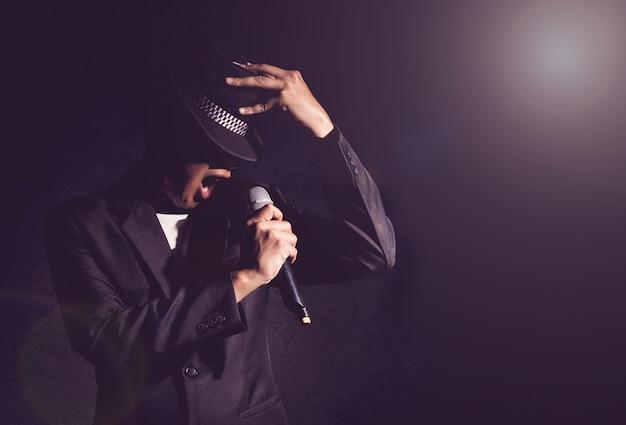 Piosenkarz ręka trzyma mikrofon i śpiew na czarnym tle