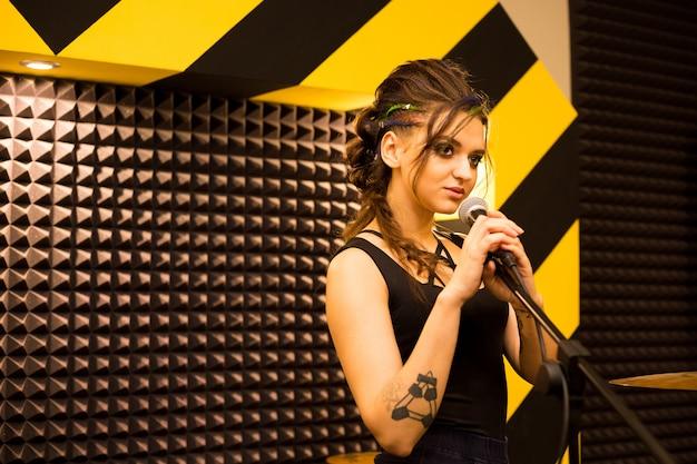 Piosenkarz rockowy nagrywający dźwięk w profesjonalnym studio z mikrofonem na pasiastej ścianie