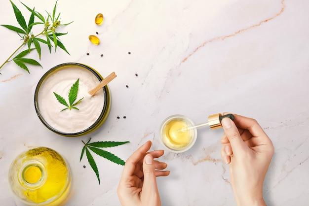 Pipeta z olejkiem kosmetycznym cbd w kobiecych dłoniach z kosmetykami, kremem z konopi i liśćmi konopi
