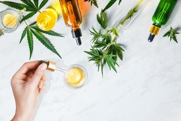 Pipeta z olejkiem kosmetycznym cbd w rękach kobiet z kosmetykami, kremem konopnym i liśćmi marihuany