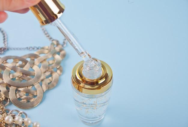 Pipetować cieczą, w której widoczne są cząsteczki złota. kropla kapiąca w czystej butelce.
