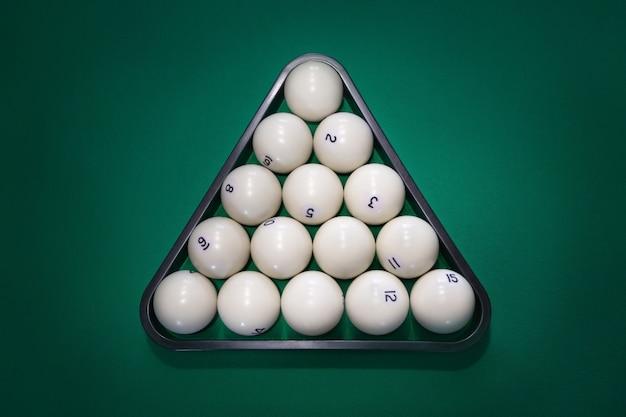 Piramida białych kul z numerami do rosyjskiego bilarda na zielonym stole, zbliżenie, widok z góry. trójkąt białych piłek na stole bilardowym
