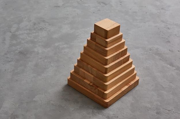 Piramida drewniane zabawki na szarym tle betonu. copyspase.