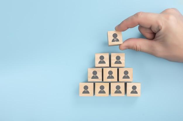 Piramida kadrowa. zasoby ludzkie, koncepcja hierarchii korporacyjnej i marketing wielopoziomowy - kompletny zespół rekruterów reprezentowany przez drewnianą kostkę przez jedną osobę lidera.