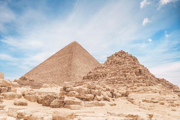 Piramida królowej znajduje się w gizie na tle wielkiej piramidy cheopsa. piękne zachmurzone błękitne niebo.