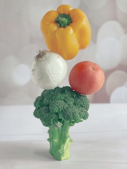 Piramida warzyw, brokułów, pomidorów, cebuli, papryki na jasnym tle. lewitacja warzyw, warzywa na parze, koncepcja zdrowej żywności.