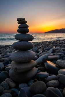 Piramida z kamieni morskich na brzegu morza o zachodzie słońca. pojęcie harmonii i równowagi.