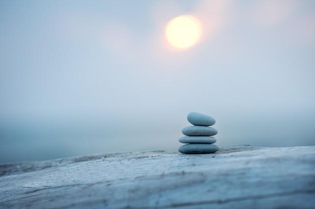 Piramida z kamieni nad morzem o świcie. zrównoważone kamienie zen.
