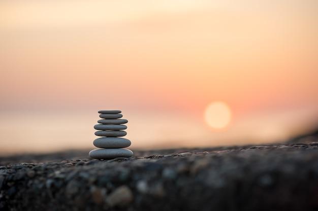 Piramida z kamieni nad morzem o zachodzie słońca. zrównoważone kamienie zen.