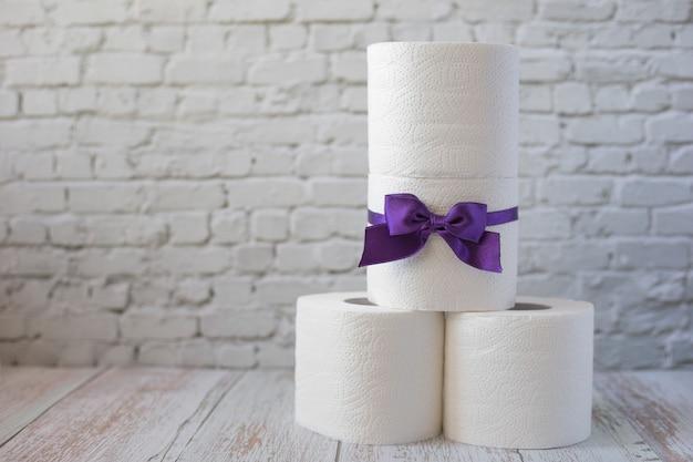 Piramida z rolek białego papieru toaletowego. rolka papieru toaletowego z fioletową kokardką