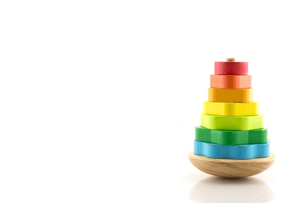 Piramida zbudowana z kolorowych drewnianych pierścieni. zabawka dla niemowląt i małych dzieci, aby radośnie uczyć się umiejętności mechanicznych i kolorów. na białym tle.