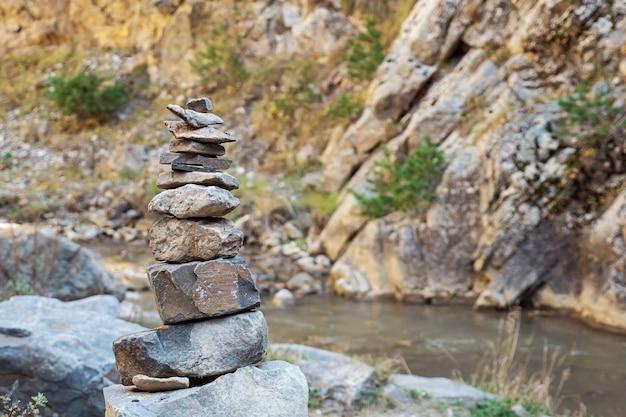 Piramidy kamieni na tle rzeki i skał. skopiuj miejsce.