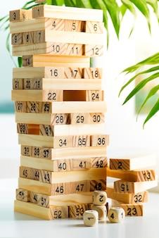 Piramyd z drewnianych klocków z numerami na białej ścianie. gra na zarabianie i rozwój.