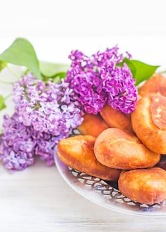 Piroshki - rosyjskie pieczone ciasto francuskie z nadzieniem z kapusty i bukietem bzu. tradycyjne rosyjskie kapusty nadziewane pieczone ciasto. chude placki z kapustą. piękne domowe ciasta z kapustą