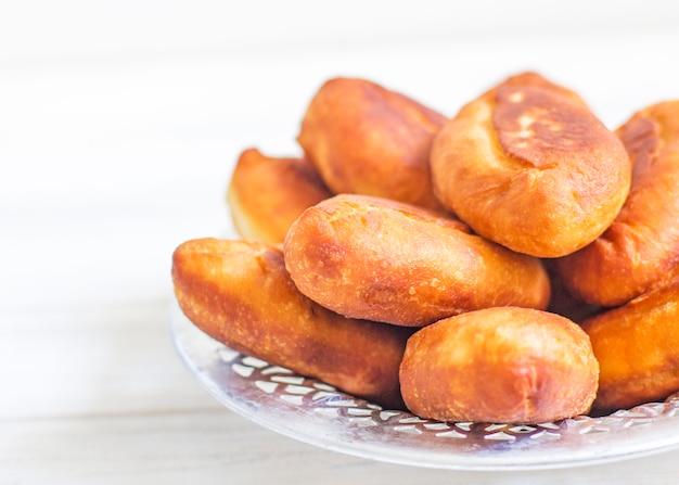 Piroshki - rosyjskie pieczone ciasto francuskie z nadzieniem z kapusty. tradycyjne rosyjskie kapusty nadziewane pieczone ciasto. chude placki z kapustą. piękne domowe ciasta z kapustą w metalowych naczyniach na białym tle
