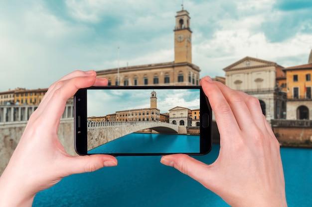 Pisa pejzaż miejski z arno rzeką i ponte di mezzo mostem, włochy. zdjęcie zrobione telefonem