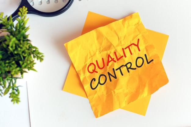 Pisanie kontroli jakości na zmiętym żółtym papierze, miejsce pracy, burza mózgów. rozogniskowanie. czerwone litery.