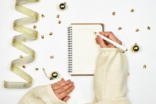 Pisanie listu do świętego mikołaja. kobieta pisze rezolucje nowego roku w notatniku. jasne miejsce do pracy