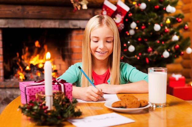 Pisanie listu do świętego mikołaja. śliczna dziewczynka pisze list do świętego mikołaja siedząc w domu z choinką i kominkiem w tle