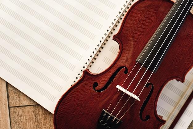 Pisanie muzyki skrzypcowej. zamknij widok piękne brązowe skrzypce leżące na arkuszach nut. lekcje skrzypiec. instrumenty muzyczne. sprzęt muzyczny.
