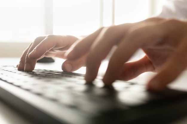 Pisanie na klawiaturze komputera z jasną flarą światła wpadającą przez okno nad jego dłońmi.