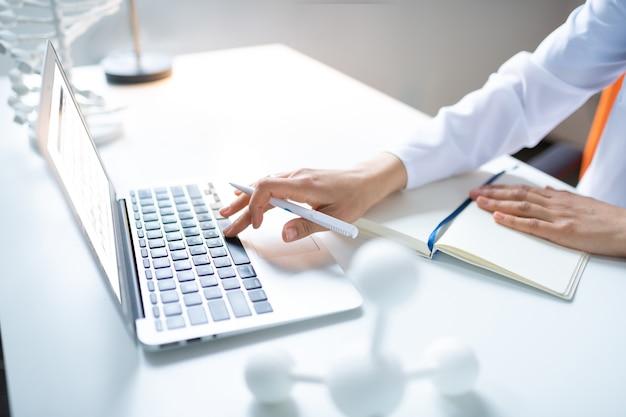 Pisanie na laptopie. zbliżenie na kobietę naukowca trzymającą długopis i piszącą coś na laptopie