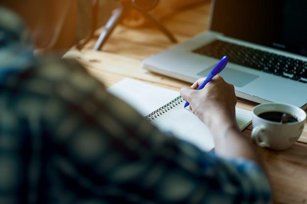 Pisanie na papierze w pracy na stole rano, pomysłów biznesowych. jest miejsce na kopiowanie.
