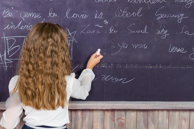 Pisanie na tablicy. dziewczyna w klasie. biurko szkoły, koncepcja edukacji. ręka trzyma kredę na tablicy szkolnej. widok z tyłu małej dziewczynki piszącej kredą na tablicy w klasie