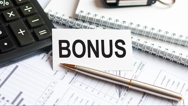 Pisanie tekstu pokazującego bonus. pisanie tekstu bonus na białej karcie papieru, czarne litery, białe tło. pomysł na biznes.