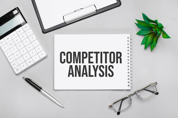 Pisanie tekstu przedstawiającego analizę konkurencji. kalkulator, długopis, plan, okulary i czarna teczka na szarym tle