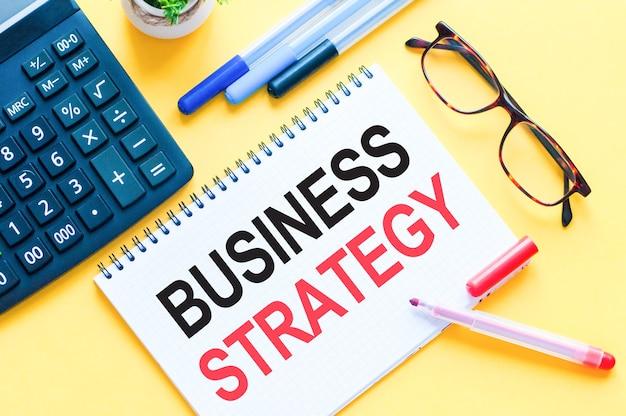 Pisanie tekstu przedstawiającego strategię biznesową. słowo strategia biznesowa na białej karcie papieru, czerwone i czarne litery. koncepcja biznesowa dla edukacji.
