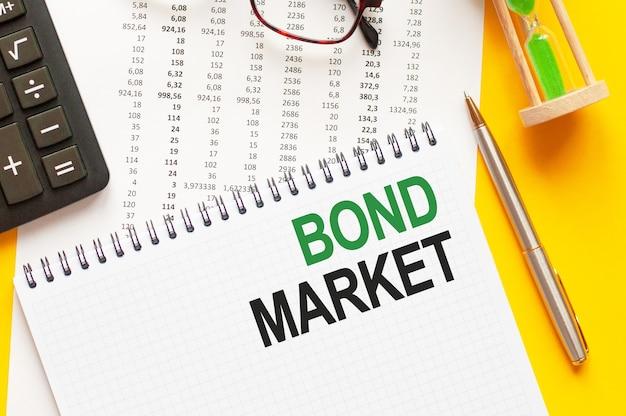 Pisanie tekstu rynek obligacji na białym notesie, zielone i czarne litery, żółte tło.