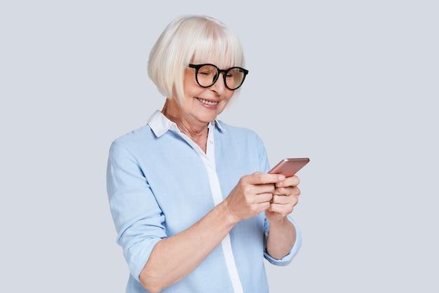 Pisanie wiadomości biznesowej. piękna starsza kobieta używająca swojego smartfona i uśmiechnięta