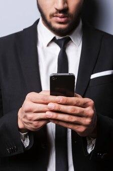 Pisanie wiadomości dla partnera biznesowego. zbliżenie: młody mężczyzna w formalwear trzyma telefon komórkowy, stojąc na szarym tle