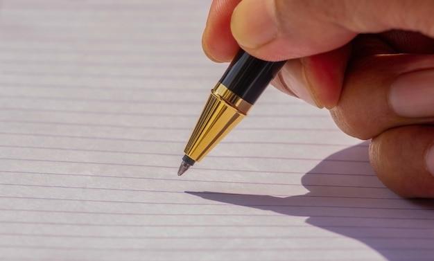 Pisanie złotym długopisem na białym papierze, wybrane skupienie