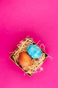 Pisanka jest koloru niebieskiego ze złotem i pomarańczowego ze złotem. dwa jajka leżą w pudełku z wiórami. malowane pisanki na różowym tle. skopiuj miejsce leżał płasko.