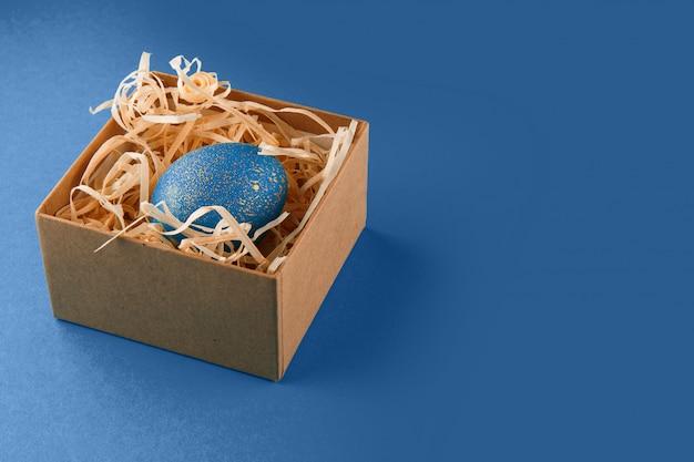 Pisanka pomalowana na niebiesko ze złotem. jajko leży w pudełku z wiórami drzewnymi. malowane pisanki na niebieskim tle. skopiuj miejsce