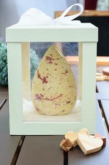 Pisanka z białej czekolady z jadalną farbą w kolorze miedzi. wewnątrz białe pudełko z kokardką ze wstążki.