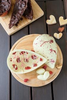 Pisanka z białej czekolady z kandyzowanymi truskawkami na drewnianym talerzu na wierzchu jajko z ciemnej czekolady z chrupiącymi migdałami widok z góry zdjęcie w pionie