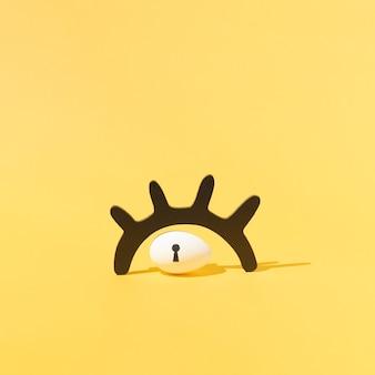 Pisanka z dziurką od klucza pod czarną drewnianą rzęsą na żywym żółtym tle. minimalistyczna koncepcja. układ kwadratowy