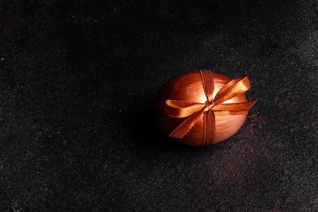 Pisanka z taśmą prezent na ciemnym drewnianym stole. przygotowanie do wakacji