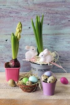 Pisanki, hiacynt w doniczce z zajączkami zabawka na drewnianym stole, wiosna