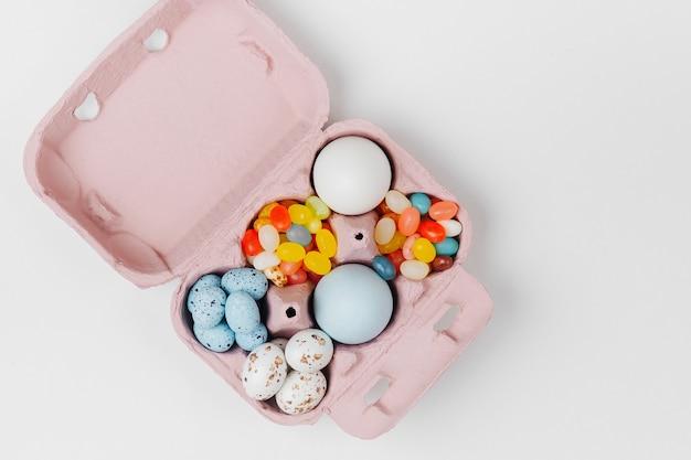 Pisanki i cukierki w pudełku. kompozycje w pastelowych kolorach. płaski układanie, widok z góry