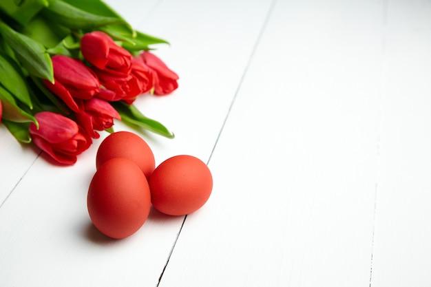 Pisanki i czerwone tulipany kwiaty na białym drewnianym stole z miejsca na kopię