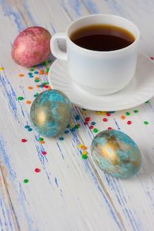 Pisanki i filiżanka kawy, wielobarwne słodycze dekoracji na drewnianym stole. wielkanocna koncepcja